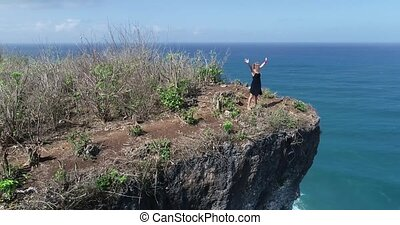Aerial view of girl standing on the beautiful cliff