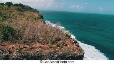 Aerial view of girl walking on the beautiful cliff