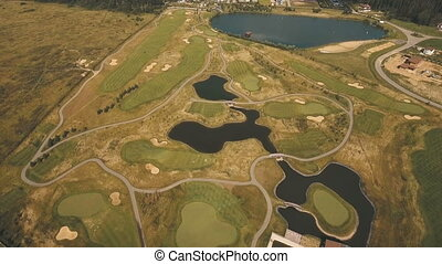 Aerial view of golf course and water.