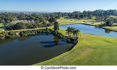 Aerial view of golf course with two water hazard dams, bunkers, and tree lined fairways