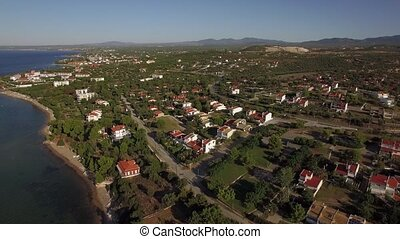 Aerial view of green lands and houses on sea coast. Trikorfo Beach, Greece