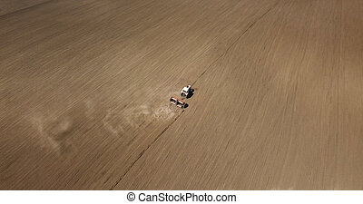aerial view of harvest field with agricultural machinery carrying out work in the field