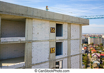 Aerial view of high residential apartment building with storey numbers on wall under construction. Real estate development.