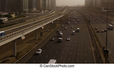 Aerial view of high-speed trains blue, which travels through the overpass along the highway with cars surrounded by skyscrapers. Dubai, UAE
