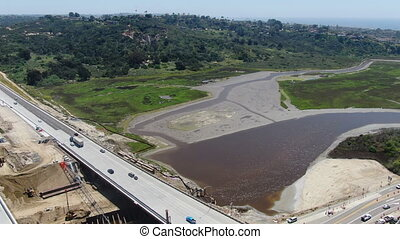 Aerial view of highway bridge construction over small river, San Diego, California, USA