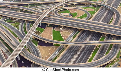 Aerial view of highway junction with traffic timelapse in Dubai, UAE, at sunset. Famous Sheikh Zayed road in Dubai downtown.