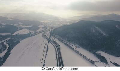 Aerial view of highway, railway and a village in winter.