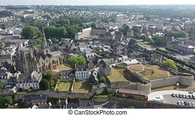 General view of French town of Guingamp in summer looking out over medieval Basilica and walls of ancient fortified chateau, Brittany