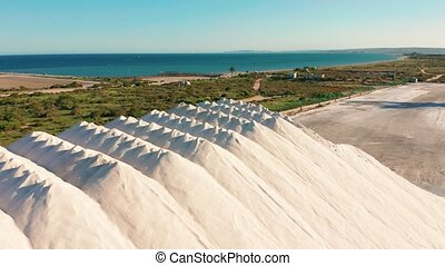 Aerial view of industrial extraction of salt in the desert, pile of salt.
