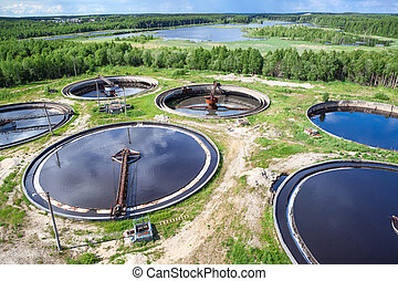Aerial view of industrial wastewater treatment plant in evergreen forest