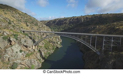 Aerial view of iron bridge over canyon with tourist walking...