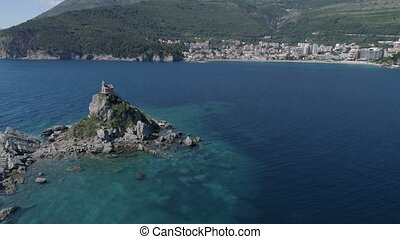 Aerial view of island with church in front of Petrovac. -...