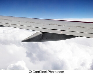 Aerial view of jet plane wing and clouds