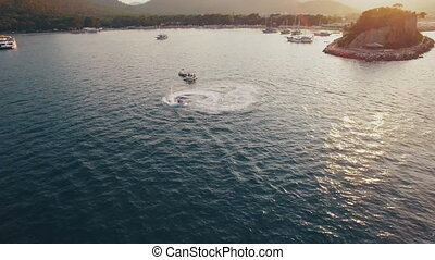 Aerial View of Jet Ski Rides in a Bay with Depp Blue Water. Sunset on Sea, Shot in 4K UHD