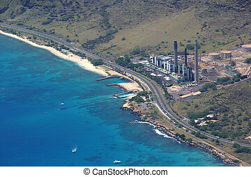 Aerial view of Kahe Point Power Plant along the ocean with highw