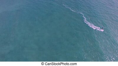 Aerial view of kitesurfer gliding across blue ocean, extreme...