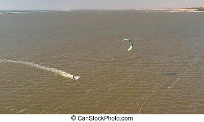 Aerial view of kitesurfer gliding and jumping across ocean