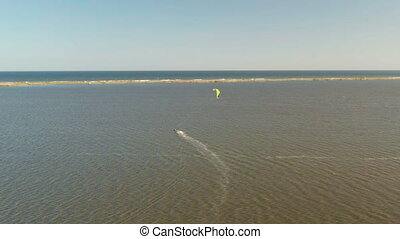 Aerial view of kitesurfer gliding and jumping across ocean.