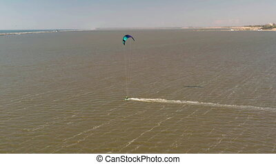 Aerial view of kitesurfer gliding and jumping across sea