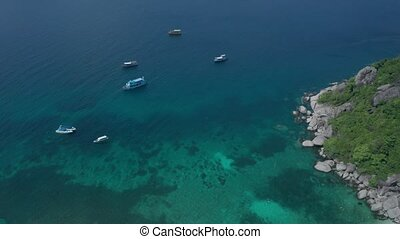Aerial drone view of lagoon sea water surface with boats near beautiful Koh Tao island in Thailand