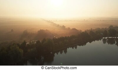 Aerial view of lake and fields on misty morning.