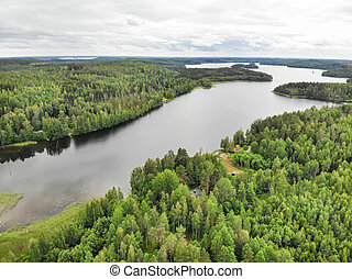 Aerial view of lake and green forest on a summer day in Finland. Drone photography