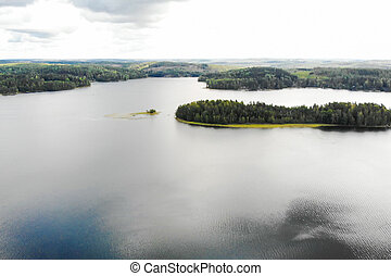 Aerial view of lake with island and forest on a summer cloudy day in Finland. Drone photography