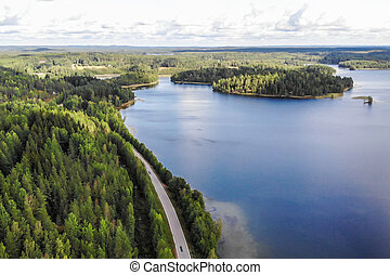 Aerial view of lake with island, road and forest on a summer sunny day in Finland. Drone photography