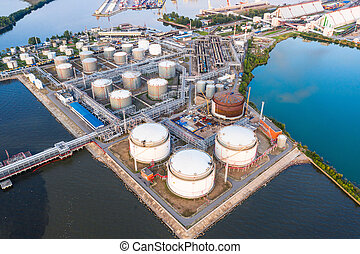 Aerial view of large fuel storage tanks at oil refinery industrial zone in the cargo seaport.