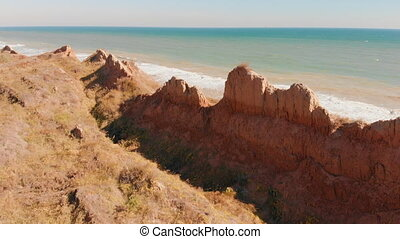 Aerial view of large rocky outcropping off sea shore. Drone...