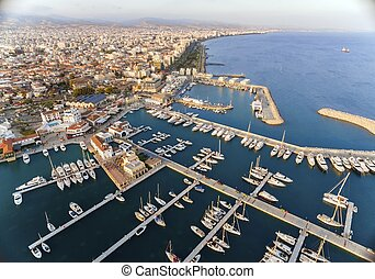 Aerial view of the beautiful Marina in Limassol city in Cyprus, the beach, boats, piers, villas, commercial area, old port (palio limani) and Molos. A very modern, high end and newly developed space where yachts are moored and it's perfect for a waterfront promenade.