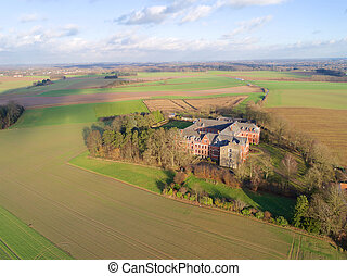 Aerial view of little farm castle surrounded by agriculture farmland et small forest