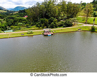Aerial view of little wood cabana next the lake in the valley, with family enjoying relax moment