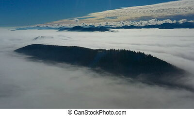 Aerial view of low clouds and mountains seen from above