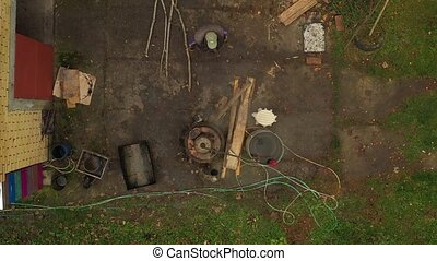 Aerial top view on man throws dry wood into the firebox of a homemade distillery making moonshine schnapps, alcoholic beverages.
