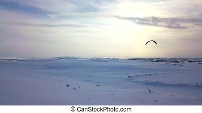 Aerial view of man flying with kite in tundra. - Aerial view...