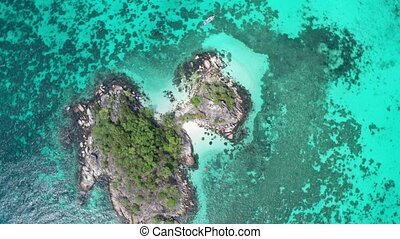 Aerial view of man kayaking in crystal clear sea water near Koh Kra island in Thailand