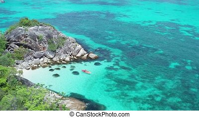 Aerial view of man kayaking in crystal clear sea water near...