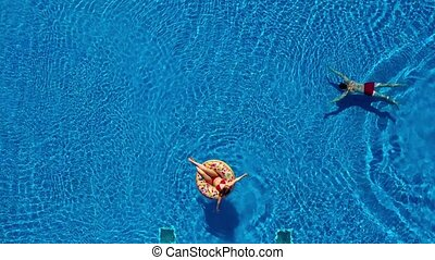 Aerial view of man swims in the pool while girl is lying on a donut pool float