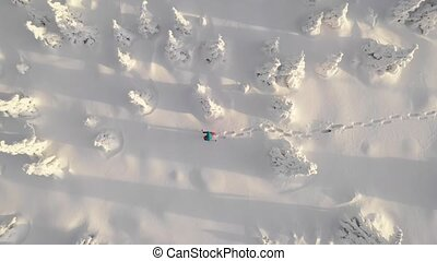Aerial view of man walking with snowshoes on white snow in winter.
