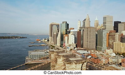 Aerial view of Manhattan in New York, America. Drone flying over the East river, Brooklyn bridge and waving on wind flag