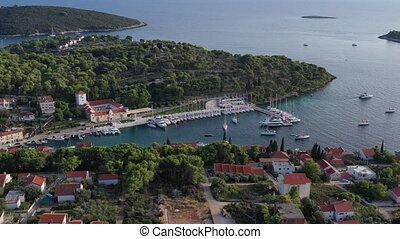 Aerial view of marina Maslinica on island Solta at sunset, Croatia, a lot of sailboats, roofs of orange color, sun reflections on water, green trees