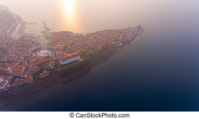 Aerial view of mediterranean coastal town at sunset.