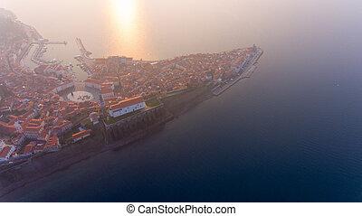 Aerial view of mediterranean coastal town at sunset.