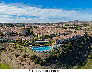 Aerial view of middle class neighborhood with identical residential subdivision house and compound swimming pool