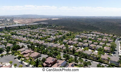 Aerial view of middle class subdivision neighborhood with residential villas and canyon preserve on the background in San Diego County, California, USA.