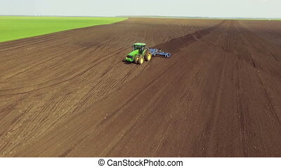 Aerial view of modern tractor plowing the soil, fertile...
