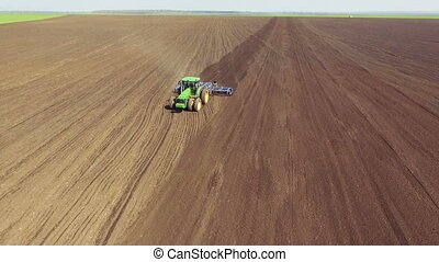 Aerial view of modern tractor plowing the soil on the...
