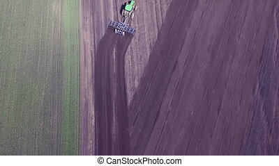 Aerial view of modern tractor plowing the fields on fertile...