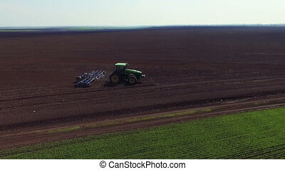 Aerial view of modern tractor plowing the fields